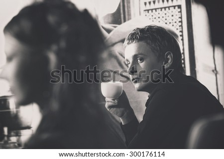 Closeup portrait of elegant macho man with cup of coffee looking at beautiful girl at retro wall background. - stock photo