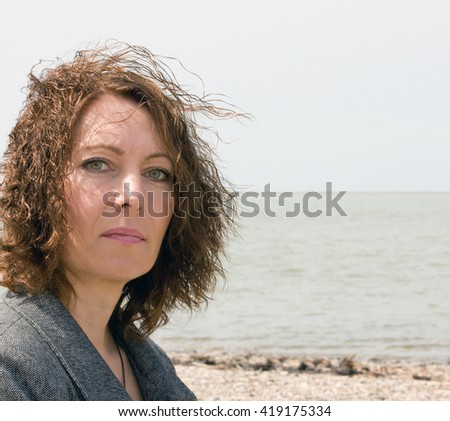 Closeup portrait of elegant middle aged woman on the beach - stock photo