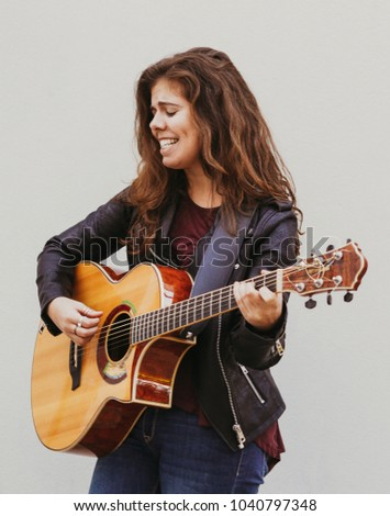 Closeup portrait of emotional young beautiful woman singing and playing guitar at wall outdoors