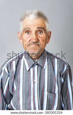 Closeup portrait of expressive old man  over gray background - stock photo