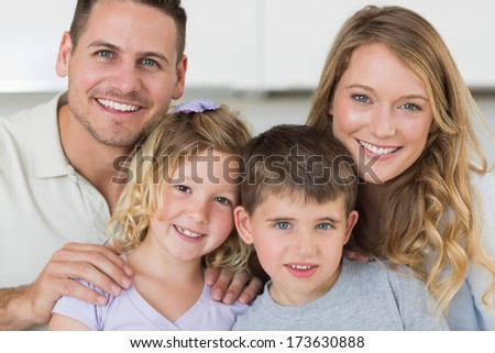 Closeup portrait of family smiling together in house - stock photo