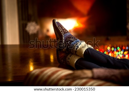 Closeup portrait of feet at woolen socks warming at fireplace in winter - stock photo