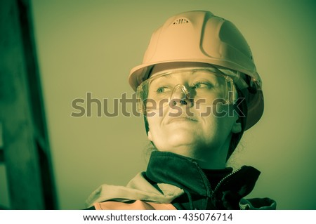 Closeup portrait of female industrial worker, engineer wearing helmet and protective glasses. Industry, manufacturing theme. - stock photo