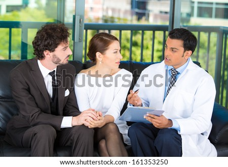 Closeup portrait of friendly,  male doctor, gynecologist, psychiatrist, oncologist, surgeon counseling young couple, on health problems, family issues. Patient visit, care, appointment, annual checkup - stock photo
