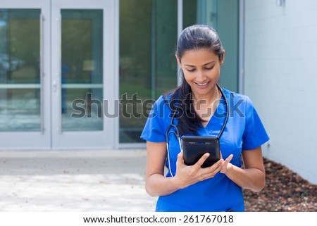 Closeup portrait of friendly, smiling confident female doctor, healthcare professional in blue scrubs with stethoscope, analyzing patient data on black digital tablet, outside hospital background - stock photo