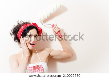 closeup portrait of funny charming beautiful pinup girl having fun paint wall with roller happy smiling & looking at camera on white copyspace background - stock photo