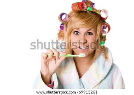 closeup portrait of funny housewife with curlers and toothbrush on white background