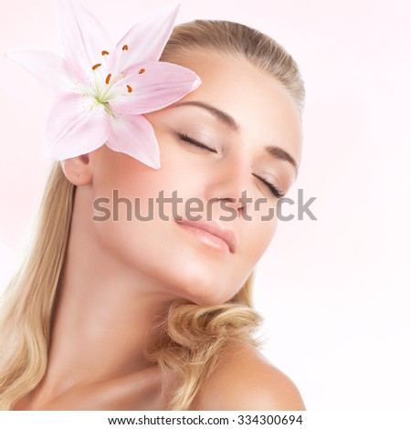 Closeup portrait of gentle cute female with pink lily flower in hair isolated on white background, closing eyes of pleasure in day spa - stock photo