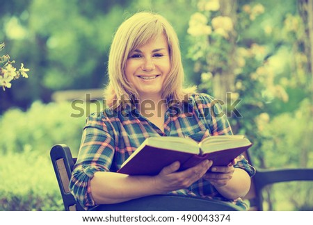 closeup portrait of glad blond mature woman enjoying her book in garden on summer day