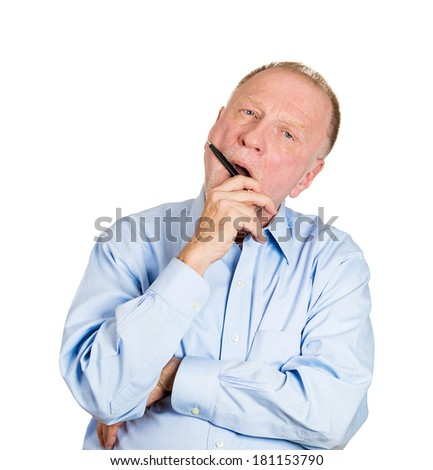Closeup portrait of goofy senior mature man playing, biting black pen, bored out of his mind, isolated on white background. Negative emotion facial expression feelings, reaction, attitude - stock photo