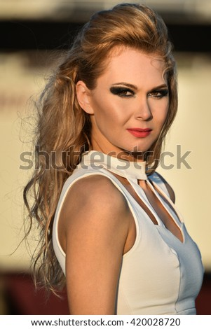 Closeup portrait of gorgeous blond girl with bright glamor make-up, spring outdoor. - stock photo
