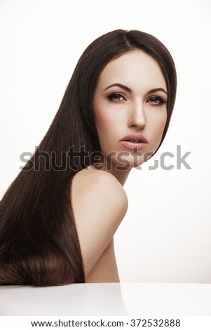Closeup portrait of gorgeous brunette woman posing in studio. Beautiful Woman with Long Healthy and Shiny Smooth Hair. Hairstyle, haircare concept.