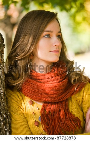 Closeup portrait of gorgeous young brunette woman in the park at autumn. - stock photo