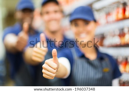 closeup portrait of group of hardware store co-workers thumbs up - stock photo