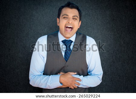 Closeup portrait of handsome, burst out laughing young business man, worker, employee, isolated gray black background. Positive human emotions facial expressions, feelings, attitude perception - stock photo
