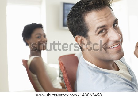 Closeup portrait of handsome businessman with female colleague in background - stock photo