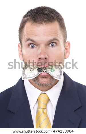 Closeup portrait of handsome Caucasian businessman eating dollar bill stuffed in his mouth with surprised eyes wide open on white background