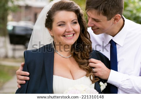 Closeup portrait of handsome groom hugging chubby bride from back