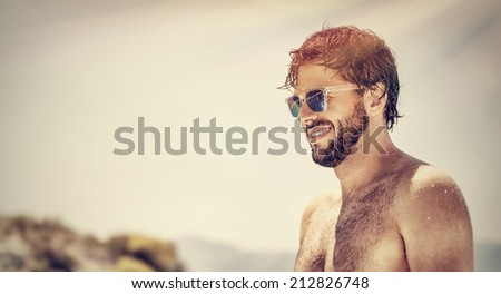 Closeup portrait of handsome man wearing stylish sunglasses, fashionable attractive model on the beach, summer vacation, freedom and pleasure concept - stock photo
