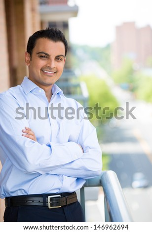 Closeup portrait of handsome man with arms folded enjoying life on outside balcony on background of trees and buildings
