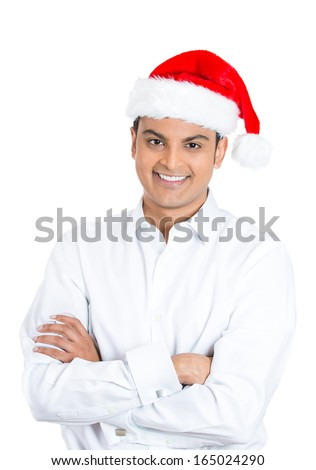 Closeup portrait of handsome smiling confident young man crossing folding arms in front of chest wearing red santa claus hat, isolated on white background. Positive emotion facial expression