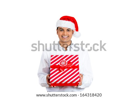Closeup portrait of handsome smiling young man wearing red santa claus hat giving present wrapped in ribbon to you camera gesture. Positive human emotion facial expression - stock photo