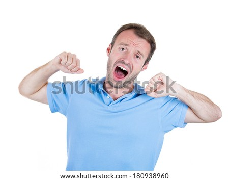 Closeup portrait of handsome, tired, bored, fatigued man in blue shirt stretching arms, back, shoulders, hands, isolated on white background. Positive human emotion facial expression feelings reaction - stock photo