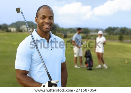 Closeup portrait of handsome young black golfer with golf club, smiling, looking at camera. - stock photo