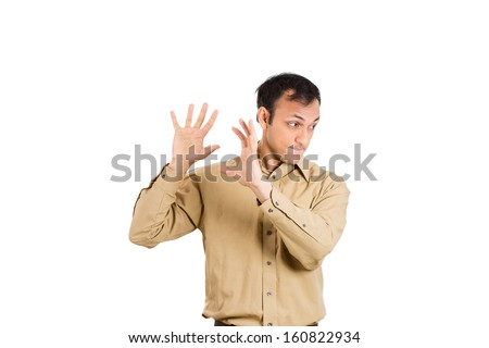 Closeup portrait of handsome young guy, man in brown shirt putting hands in the air as if to say, i don't want to hear it anymore isolated on white background with copy space.  Negative human emotions - stock photo