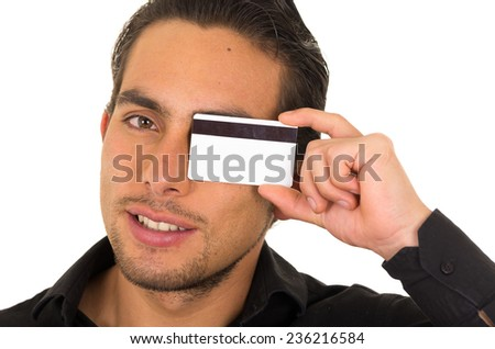 closeup portrait of handsome young man holding credit card in front of his eye isolated on white - stock photo