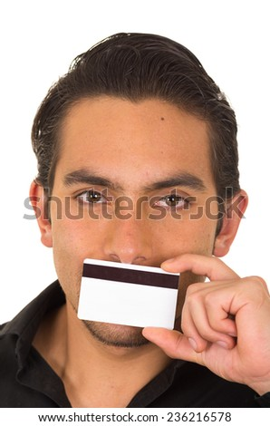 closeup portrait of handsome young man holding credit card in front of his mouth isolated on white - stock photo
