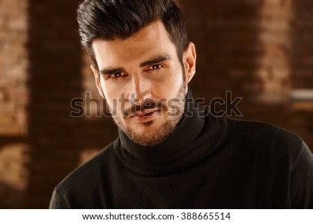 Closeup portrait of handsome young man looking at camera in turtleneck pullover. - stock photo