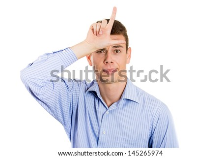 Closeup portrait of handsome young man sticking his tongue out with loser sign on forehead, isolated on white background with copy space - stock photo