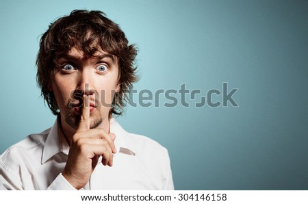 Closeup portrait of handsome young shocked business man, silent young business man shows the gesture of silence. Positive human emotion, facial expression sign symbol. - stock photo