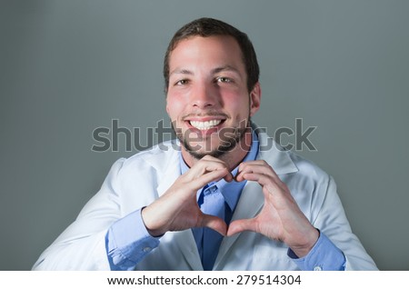 Closeup portrait of handsome young smiling doctor making a heart with hands over gray background - stock photo