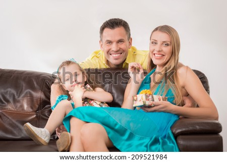 Closeup portrait of happy adorable Caucasian family with little girl, beautiful mother and daughter smiling holding presents, at home - stock photo