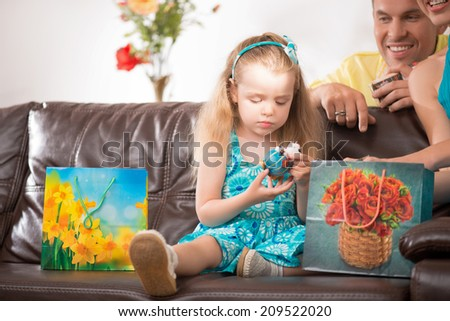 Closeup portrait of happy adorable girl, little daughter sitting on couch with heap of presents, beautiful blonde mother and handsome father smiling at home - stock photo