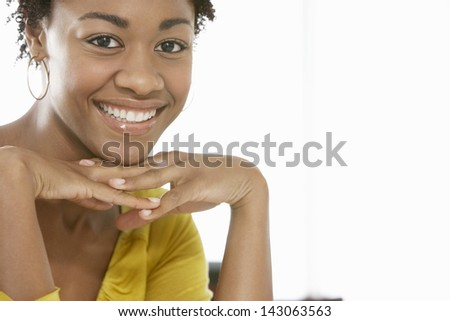 Closeup portrait of happy African American woman with hands on chin isolated on white background