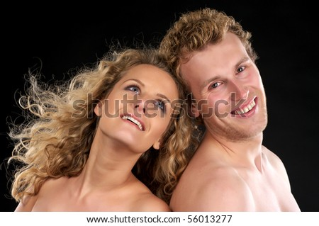 Closeup portrait of happy beautiful naked couple with curly hair over black background - stock photo