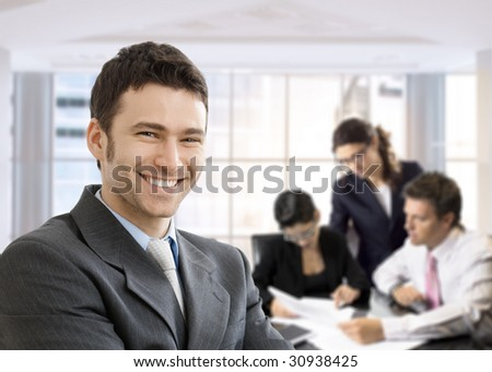 Closeup portrait of happy businessman, looking at camera, smiling. Business team working in the background, sitting at desk. - stock photo