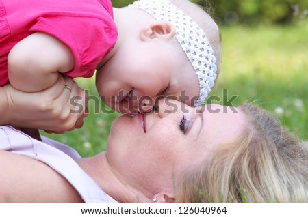 Closeup portrait of happy child with her mother in the park - stock photo