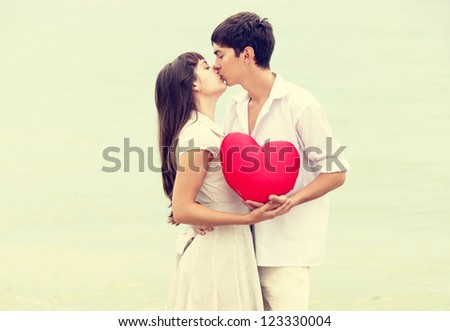 Closeup portrait of happy couple at the beach with heart.