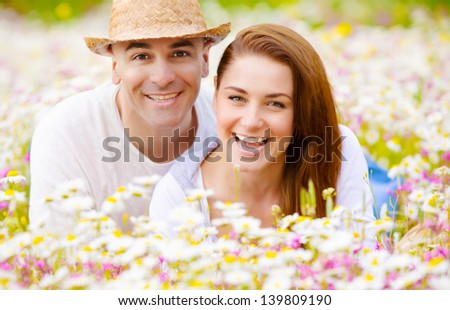 Closeup portrait of happy couple lying down on fresh daisy field, romantic date, summer vacation, love concept