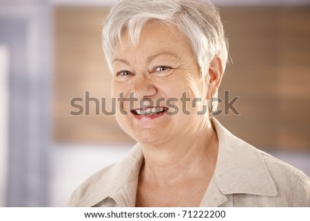 Closeup portrait of happy elderly woman with white hair, looking at camera, smiling.?