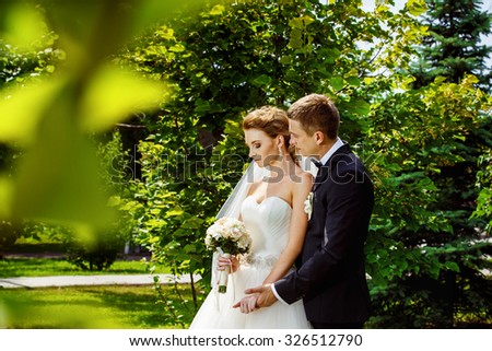 Closeup portrait of happy elegant groom embracing beautiful bride with wedding bouquet at green bright summer park background. - stock photo