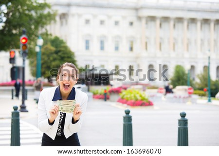 Closeup portrait of happy, excited corrupt politician in washington dc, holding dollar bills isolated on Capitol building background. Human emotions and facial expressions. Greed, politics concept - stock photo