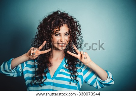 Closeup portrait of happy, excited successful young woman giving peace, victory or two sign, isolated on green background. Positive emotions, face expressions, feelings, attitude, reaction, perception - stock photo