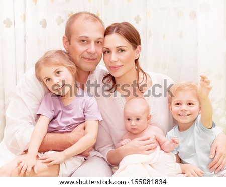 Closeup portrait of happy family at home, young parents spending time with adorable children, relaxed together, love and happiness concept - stock photo