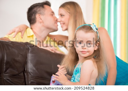 Closeup portrait of happy family, little cute daughter smiling while her parents caressing each other on background, home interior - stock photo