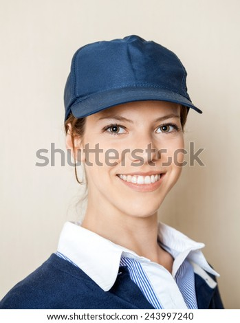 Closeup portrait of happy female concession worker against beige wall at cinema